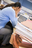 Businesswoman in cubicle with stacks of files
