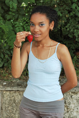 Young girl with an afro eating a strawberry