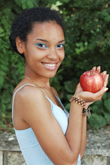 Beautiful black young woman with fresh fruit red apple