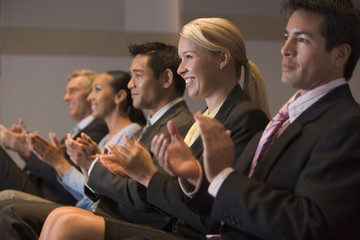 Five businesspeople applauding in presentation room
