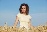 Young woman having pleasure in grain field poster