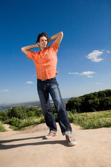 Young man winning on peak of a mountain. Against a blue sky