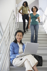 Teacher using laptop on stairs in school, students in background