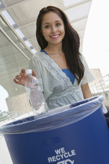 Young woman recycling plastic bottle, portrait