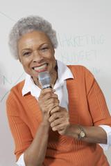 Female teacher using microphone near white board