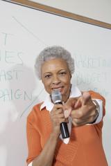 Female teacher using microphone, pointing near white board