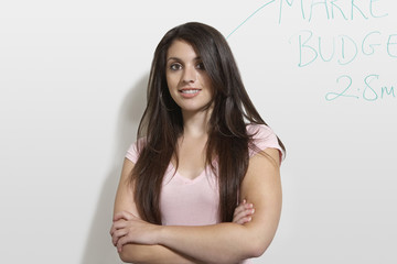 Female student standing by white board, portrait