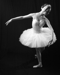 The girl in a ballet suit on a black background