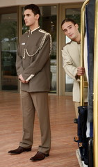 Bellboy delivering luggage to hotel with doorman standing by
