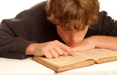 fourteen year old boy engrossed in reading book