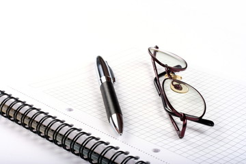 Notepad with eyeglasses and pen isolated on white