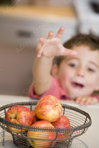 Young boy getting apple off counter