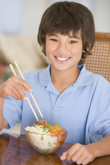 Young boy eating chinese food smiling