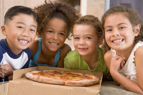 Four young children with pizza smiling