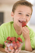 Young boy eating strawberries in living room smiling