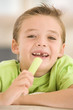 Young boy eating celery in living room smiling
