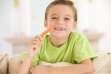 Young boy eating carrot stick in living room smiling