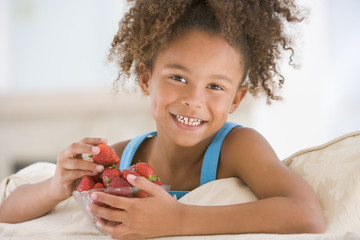 Young girl eating strawberries smiling