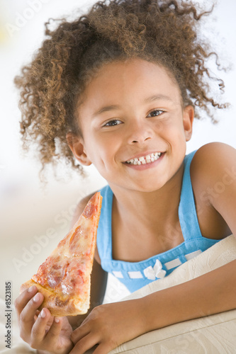 Young girl eating pizza slice in living room smiling