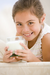 Young girl drinking milk in living room smiling