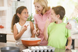 Fototapety Woman and two children baking and smiling