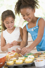 Two girls decorating cookies smiling