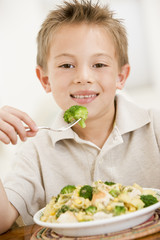 Young boy eating pasta with brocolli smiling