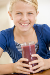 Young girl drinking juice smiling