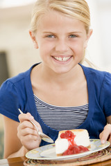 Young girl eating cheesecake smiling