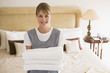 Maid holding towels in hotel room smiling - 8524927