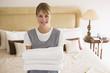 Leinwanddruck Bild - Maid holding towels in hotel room smiling