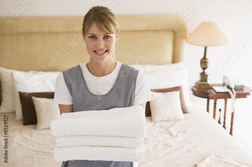 Leinwanddruck Bild Maid holding towels in hotel room smiling