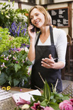 Woman working at flower shop using telephone and smiling