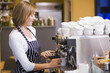 Woman making coffee in restaurant smiling