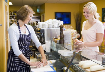 Woman standing at counter in restaurant serving customer smiling