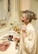 Woman sitting at the dressing table and applying cosmetics