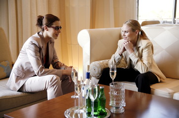 Two girls talking during a business meeting
