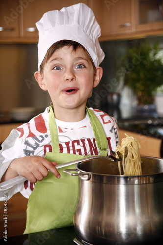 Boy cooking spaghetti
