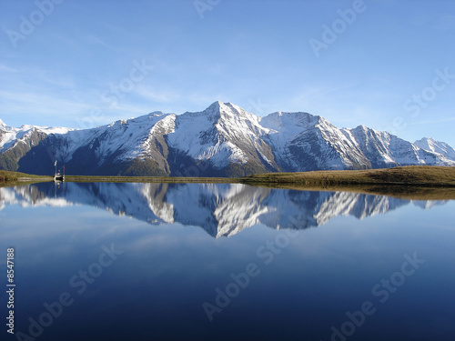 Reflection in the water of the quiet Bettmersee Lake in Valais