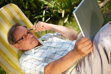 Senior man using laptop outdoor