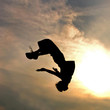 silhouette of jumping man against sky and clouds