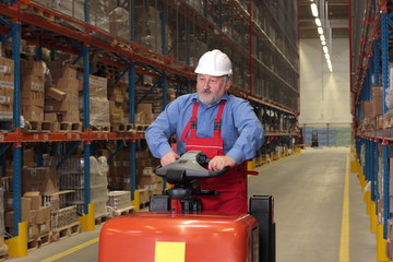 A senior worker driving the fork lift