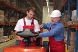 A senior worker teaching  junior the operation of a fork lift poster
