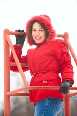 pretty woman on metallic ladder in winter