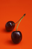 two cherries on vivid orange background with shadow poster
