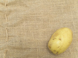 Single potato at the brown linen poster