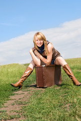 laughing girl sitting on the suitcase