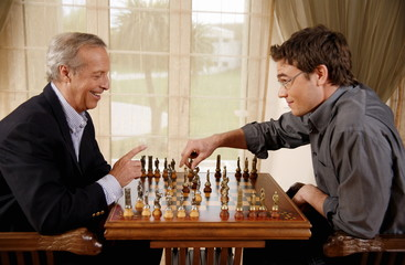 Mature man and younger man playing chess