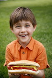 Little boy holding a hot dog