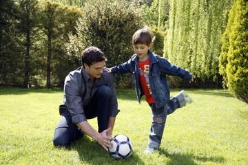 Man teaching boy to play soccer